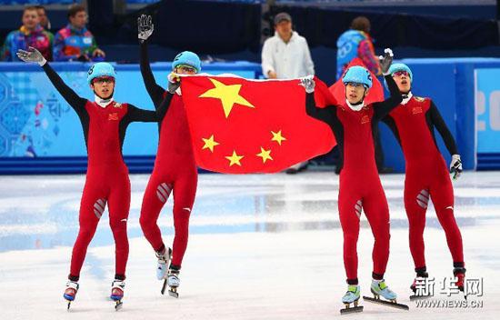 图为2月21日,在2014索契冬奥会短道速滑男子5000米接力比赛后,中国队队员手举国旗庆祝。新华社记者龚兵摄 短道男子5000米接力决赛出发后的第一个弯道发生了碰撞,中国队第一棒武大靖和一名荷兰选手摔倒后滑出赛道,但是中国队没有放弃比赛,继续赶超对手获得铜牌,追平冬奥会历史上的最好成绩。