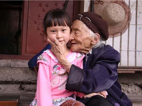 滇缅公路筑路女工梅平贞(右)和曾孙女婷婷深情相拥。