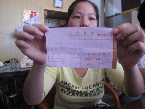 市民邓桔云向我们出示装修方开具的收款收据(记者 李景辉摄)