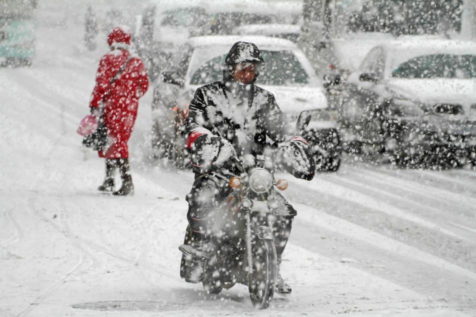 """山东烟台遭遇强降雪 民众出行变""""雪人"""""""