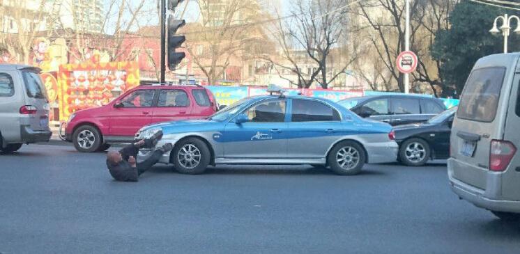 杭州一男子翘腿叼烟躺地上碰瓷出租车