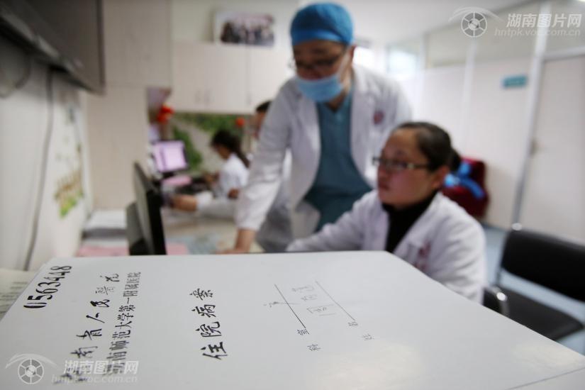 医生办公室,贺鑫与同事讨论产妇术后的伤口恢复问题.