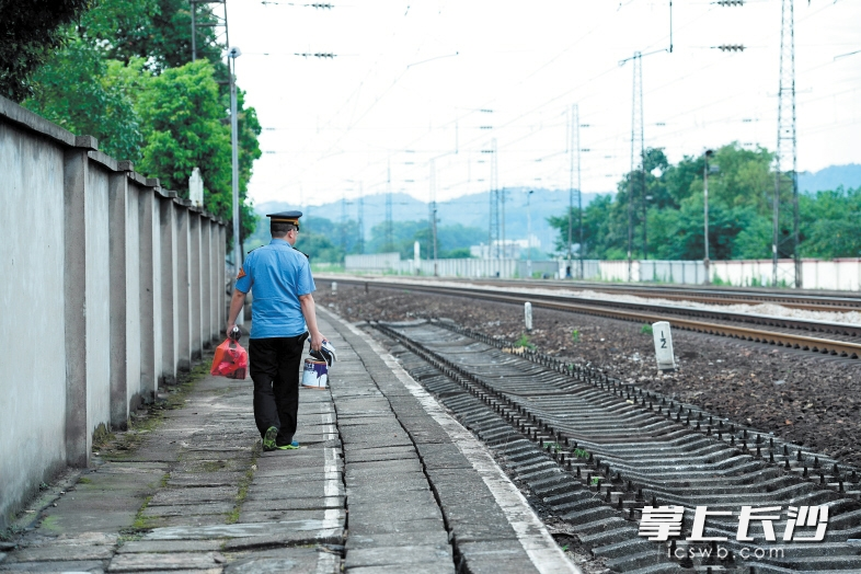 完成了最后一班岗,谭智龙提着放在站里的个人物品走出车站。