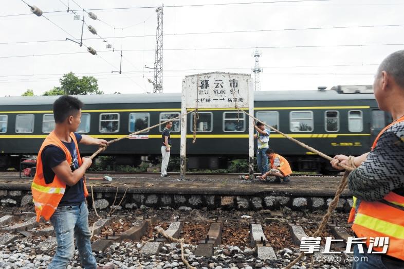 昨日中午,施工人员将铁轨旁的暮云市站站牌拆除。