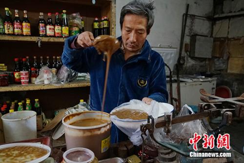 王老板在给顾客舀酱。<a target='_blank' href='http://www.chinanews.com/' >中新网</a>记者 李卿 摄