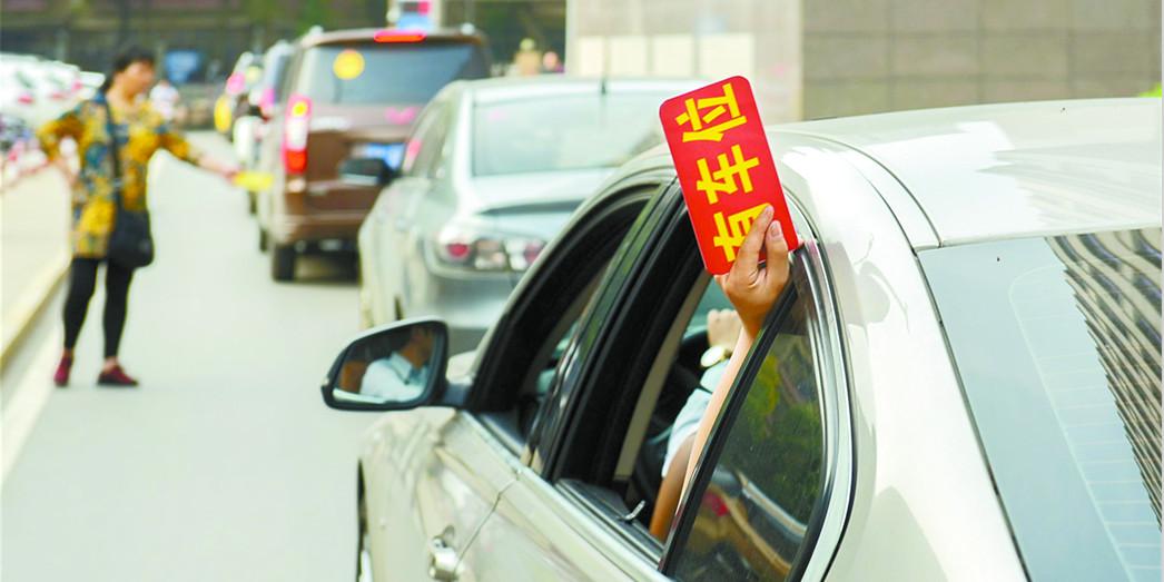 长沙:医院车位紧张 附近居民自制停车牌揽客