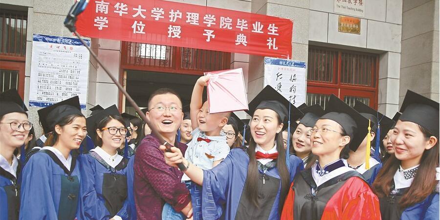 美女毕业生带着丈夫和孩子一起参加毕业典礼