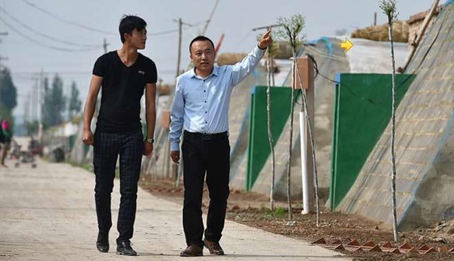 在宁夏中卫市,万立军(右)和员工查看蔬菜大棚(5月21日摄)。新华社记者 李然 摄