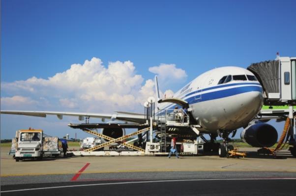 飞机降落后,工人进行集装箱装卸作业.图/李芯慧