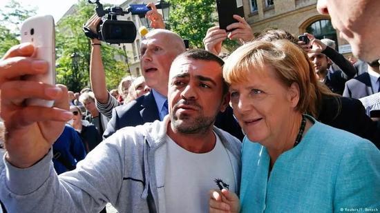 资料图片:默克尔总理与难民亲切合影。(路透社)