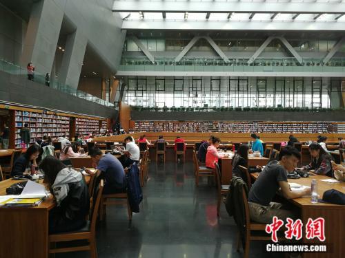 十一黄金周期间,不少人选择在图书馆度过难得的休闲时光。图为假期期间国家图书馆里的阅读者。中新网记者 张尼 摄