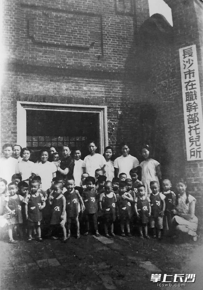 """这是1951年长沙市在职干部托儿所的小朋友与老师的合影。当年长沙市兴办托儿所的目的是""""为了更好地使母亲们安心地工作""""。"""