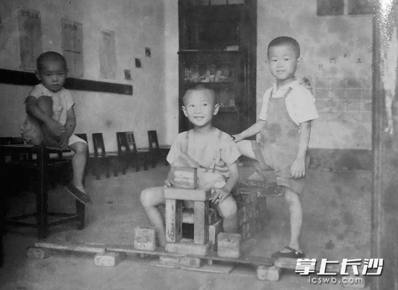 """1951年,时值抗美援朝,长沙一家幼儿园内,三个孩子用自己的双手做成一架""""战斗机"""",中间的孩子代表战斗机驾驶员。"""