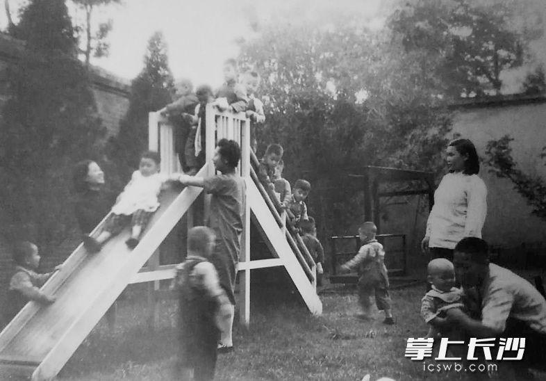 """滑梯在长沙俗称""""梭梭板""""。这是上世纪50年代长沙一家托儿所内幼儿们在老师的看护下玩""""梭梭板""""。当时,长沙托儿所内儿童游戏设施并不多,但每一样都会让孩童们异常开心。"""