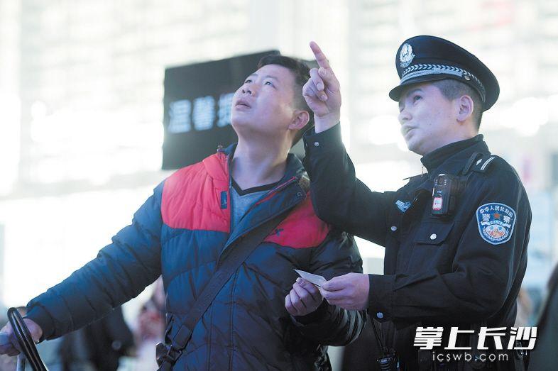 昨日上午,长沙火车南站,许伟正在帮一名旅客查看车次表,并告诉他如何上车。长沙晚报记者 黄启晴 摄