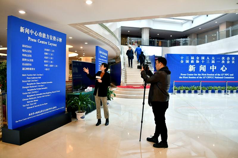 2月27日,两名记者在全国两会新闻中心内采访拍摄。