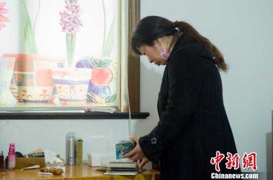 妻子王红霞翻阅相册 傅颖川 摄