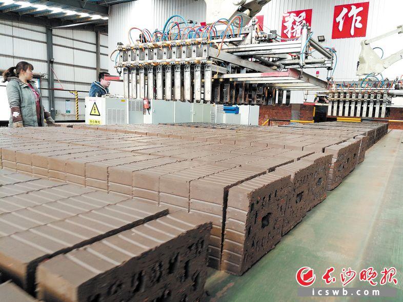 梅湖建材采用2台机器人代替人工码垛,最大抓取重量达800千克,工作效率相当于20个工人。均为 伍玲 摄
