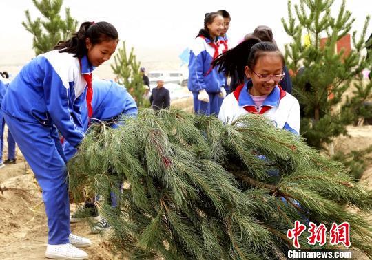 图为学子参与植树。 张添福 摄
