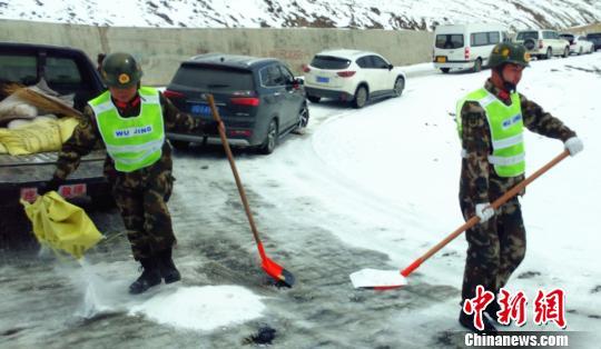 武警某部交通三支队驻左贡县中队官兵向结冰路面抛撒工业盐 路凯 摄