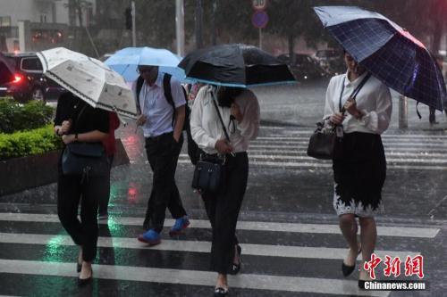 5月7日,广州街头,民众撑伞行走在雨中。当日,受强降水云团影响,广东全省共有49个暴雨预警信号生效。 <a target='_blank' href='http://www.chinanews.com/'>中新社</a>记者 陈骥旻 摄