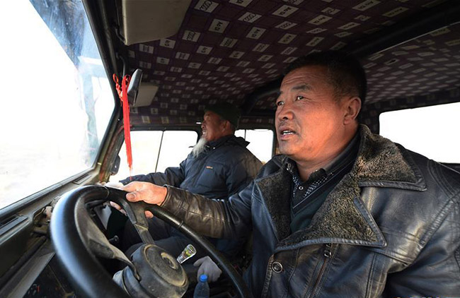 王天昌(左)、王银吉父子开车到沙漠里治沙。图片来源于网络