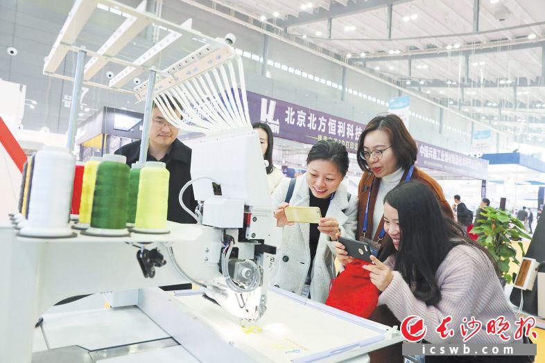 第二届中国(长沙)智能制造峰会上,树根互联展台展示的智能织布机吸引众人拍照。