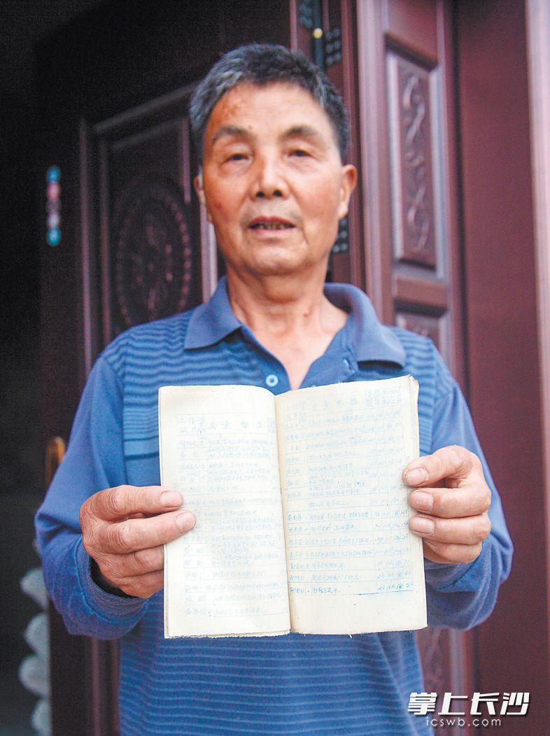 """当年村集体的一本《劳动定额》被李取如留了下来,他笑了笑说:""""现在也算是古董了,留着做个纪念。""""长沙晚报记者 钱娟 摄"""