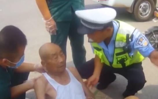 老人骑车街头晕倒 路过行人边喂水边冰敷降温救助