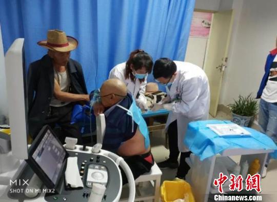 图为:王俊在松藩县人民医院为病人进行治疗 浙江临海市第一人民医院供图 摄