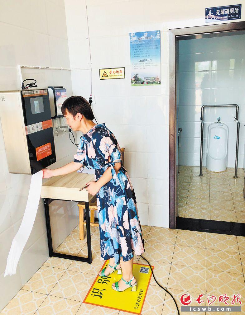 """市民站在黄色识别区内,朝墙上的方盒子瞄一眼,便可刷脸""""刷""""出免费卫生纸。 均为长沙晚报记者李卓 摄"""