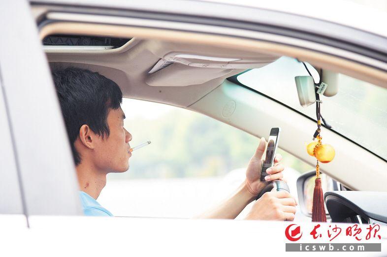 昨日上午,咸嘉湖路上,一名驾驶人在驾车途中一边抽烟一边玩手机。长沙晚报记者 刘琦 摄