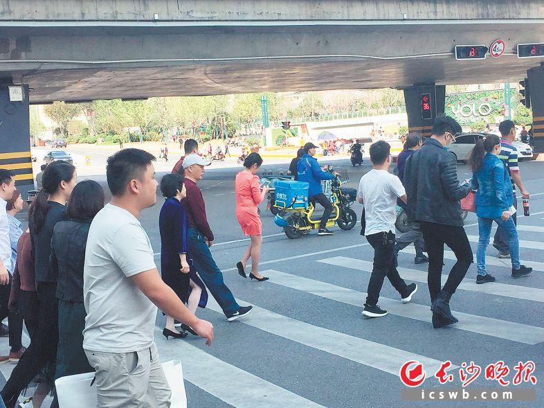 一名穿红裙的女子、一名戴口罩的小伙子过马路时低头刷手机。 长沙晚报记者 朱炎皇 摄