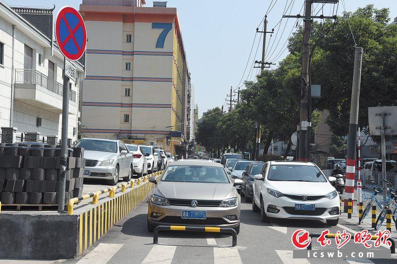 """原有的一条行车道和非机动车道,也被""""先锋厅停车场""""围起来用于停车。长沙晚报记者 刘琦 摄"""