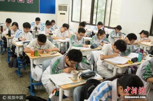 资料图:高中课堂学生在听课、做题。图片来源:视觉中国