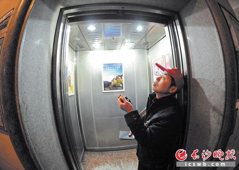 王府花园小区电梯内,电梯维保人员正举着手电筒对电梯内的线路进行仔细检查。长沙晚报记者 王志伟 摄