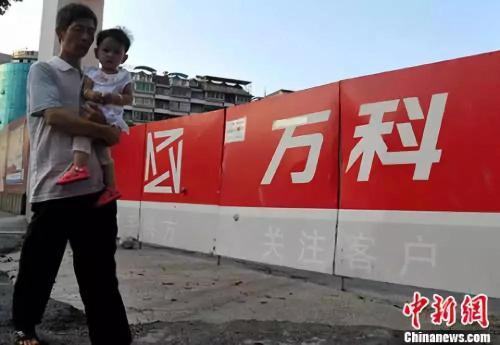 资料图:福州民众从万科楼盘工地旁经过。<a target='_blank' href='http://www.chinanews.com/'>中新社</a>记者 张斌 摄