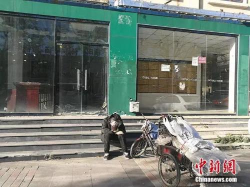 """2018年10月,燕郊""""售楼一条街"""",已经关门的链家门店前停着一辆装货的三轮车,车的主人坐在地上,把头深深地埋进臂弯。<a target='_blank' href='http://www.chinanews.com/' >中新网</a>记者 邱宇 摄"""