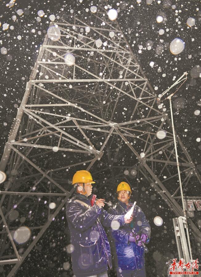 2018年12月30日7时左右,大雪一夜未停,胡波(右)和付兵(右)在铁塔下测量温度、风速和湿度。在天气最恶劣的时候,他们每两小时就要监测一次。 文/图湖南日报华声在线记者 童迪 通讯员 刘辉军 桃江县乌旗山一山岭垭口处,有个简陋的灰色水泥房,这是500KV(超高压)江城线0602号铁塔固定观冰哨,国网湖南输电检修公司输电运检三分部的胡波与付兵是这个观冰哨的主人。 2018年12月29日晚,当地下起了大雪。30日凌晨起,胡波、付兵两人每两小时就要到铁塔下监测一次实时冰情。监测的内容包括测量温度、湿度、风速