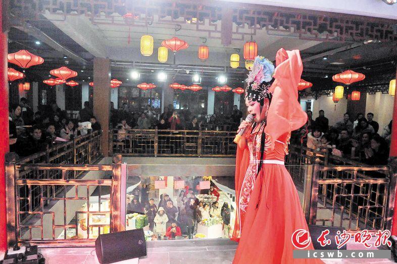 昨日下午,长沙太平街湘妙汇的舞台上,花鼓戏演员正在倾情表演,吸引不少市民和游客观看。长沙晚报全媒体记者 贺文兵 摄