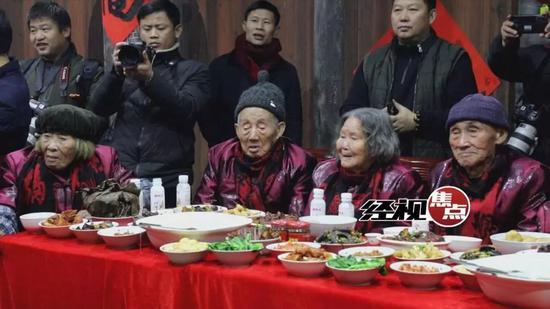 老人们一边吃着年饭,一边欣赏新田传统的南岳狮子和新田花灯戏表演。