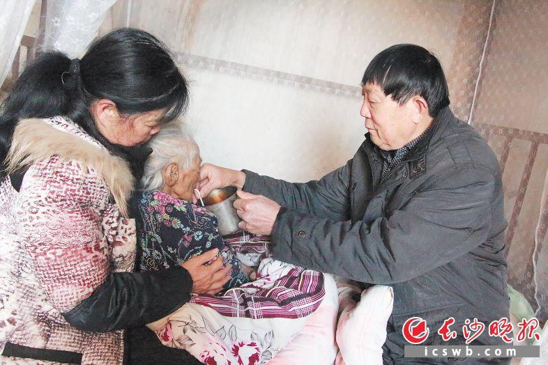 谭明照(右一)在给岳母喂茶。长沙晚报通讯员 魏枫 全媒体记者 贺文兵 摄影报道