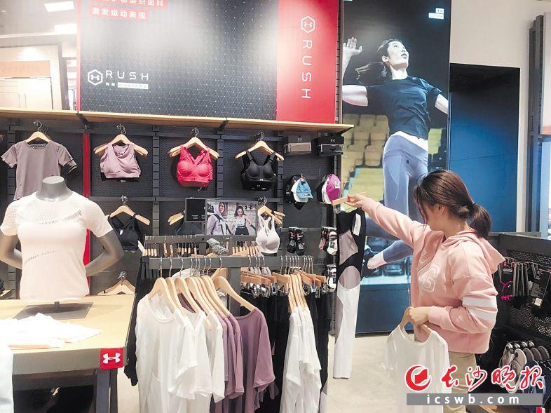 图为健身爱好者在精心挑选时尚运动装备。 长沙晚报全媒体记者 周丛笑 摄