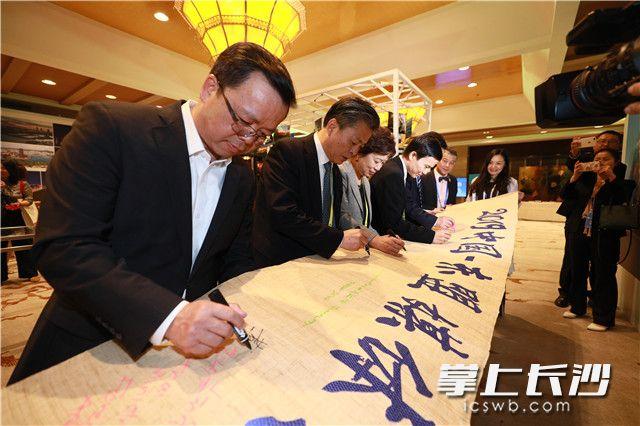 与会嘉宾在浏阳夏布织就的横幅上签名留念。