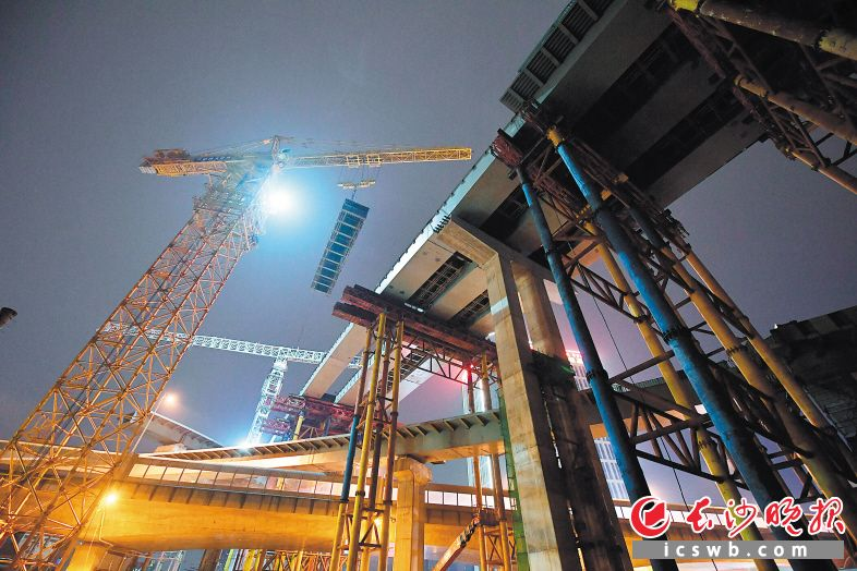 今日零时许,湘府路快改工程主线万家丽立交桥最后一段钢箱梁进行吊装施工。 长沙晚报全媒体记者 王志伟 摄