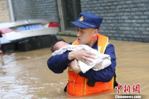 6月10日,江西省吉安县梅塘乡渡口村,消防员蹚着齐腰深的洪水,小心翼翼地将婴儿转移到安全地带。 郭清云 摄