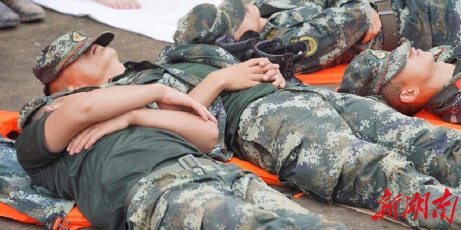 抗洪一线官兵连夜奋战12小时 席地而睡