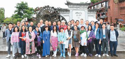 图为参加采风活动的部分华文媒体代表在丽江古城大水车前合影留念。