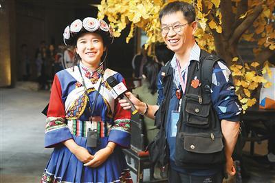 华文媒体代表(右)在体验用VR全景展现的纳西史诗《创世纪》后,对纳西族工作人员进行采访。杨浩明摄