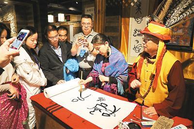 """华文媒体代表(右二)在纳西创世纪文化体验中心学写东巴文""""福""""字。"""